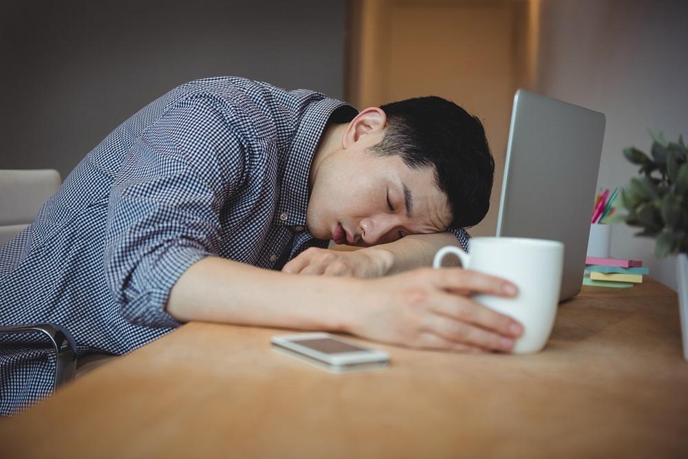 Man slapend achter zijn computer thuis