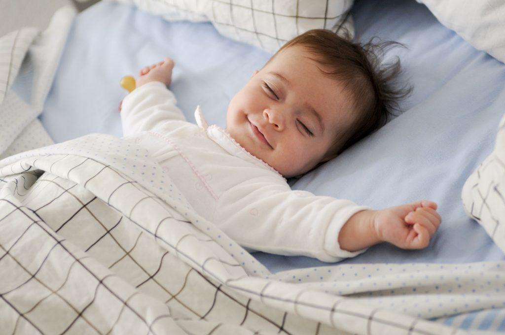 Lachende, uitgeslapen baby in bed