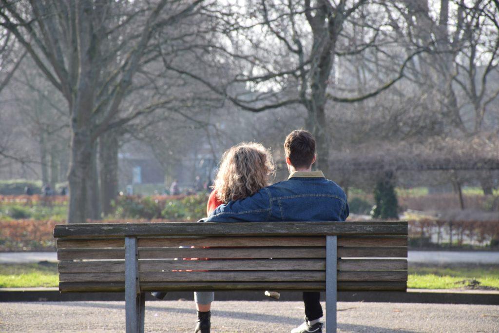 Gelukkig samen op een bankje in het park tijdens de lockdown. Samenzijn met vrienden, familie of partner creëert geluk. Daglicht en natuur creëert ontspanning.