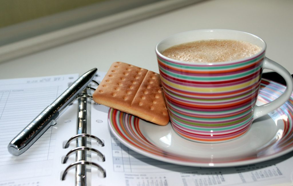 Foto van koffie en koekje op agenda, om productiviteit zonder stress te illustreren
